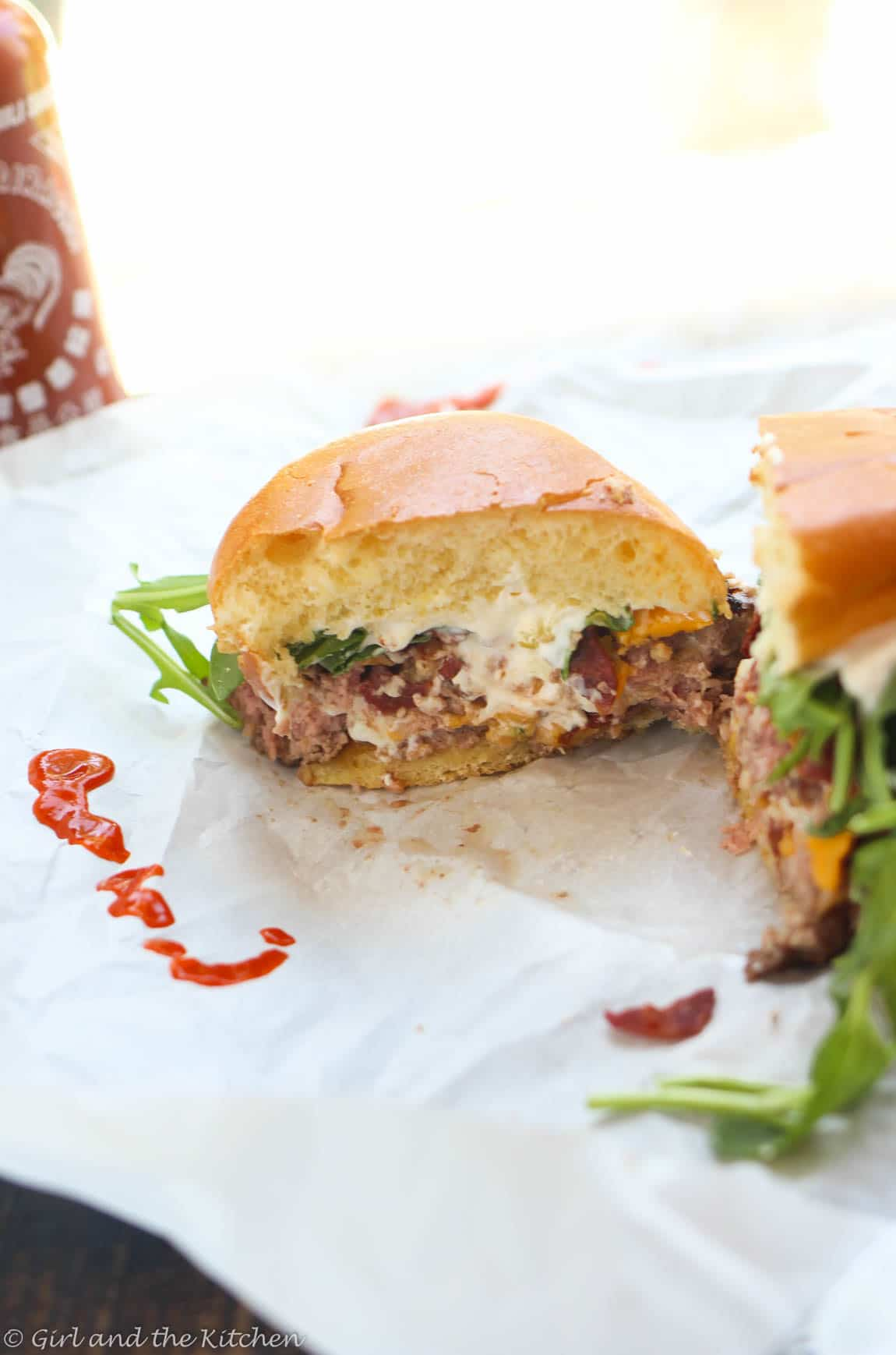 Meet the ultimate stuffed burger to rule your BBQ!!! This juicy stuffed burger oozes with melted cheeses and is topped with crispy bacon and peppery arugula