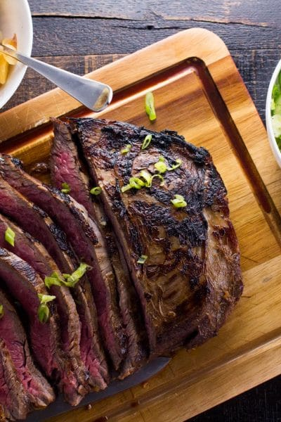This incredibly tender marinated flank steak is the perfect combination of sweet and tangy. The whiskey and soy in the recipe is the perfect combination of east meets west!