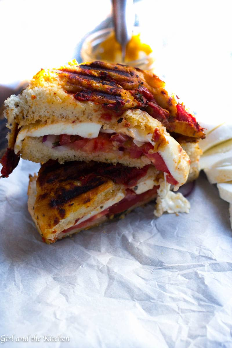 This spicy caprese panini boasts a super tender and crunchy focaccia bread and is spread with a deliciously spicy and creamy aioli.  Prepare to meat the ultimate panini.