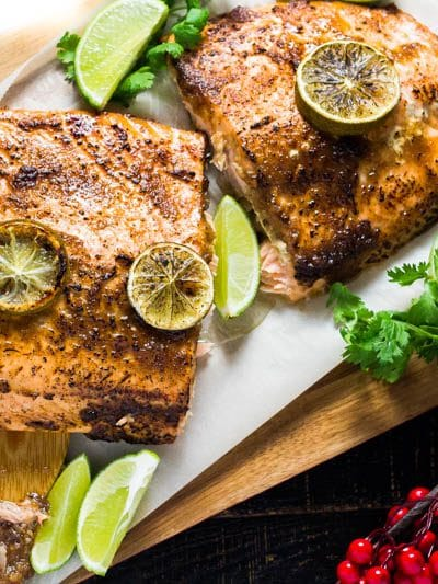This Whole Roasted Salmon s a showstopper! It is glazed with a beautiful sweet and tangy chill garlic glaze that pack a ton of unique flavors all in one bite. Classic Thai tamarind paste pairs up with molasses and chillies for a delicious salmon that serves as an incredible table centerpiece with minimal effort.