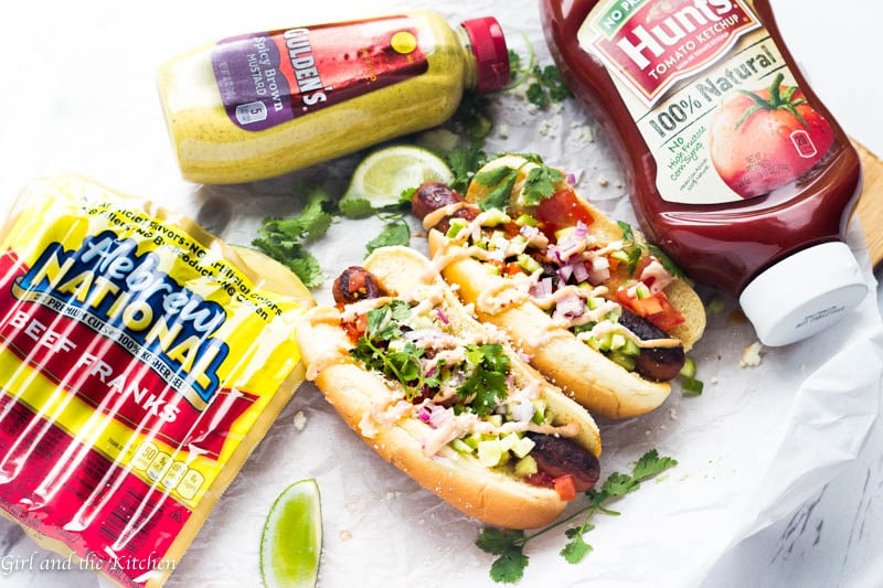 These perfectly charred Baja Style Mexican Hot Dogs are ideal for any summer cookout rain or shine! Learn my trick to getting the most tender and juicy dogs without sacrificing on the char factor! Topped with a gorgeously bright cucumber salsa and a spicy mustard aioli, these hot dogs are perfect for a summer BBQ crowd!
