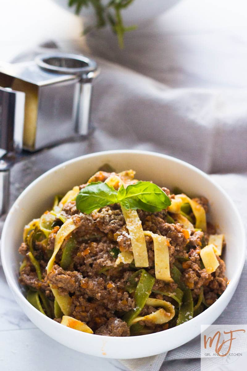 "This delicious and hearty Instant Pot Bolognese cooks up in under an hour and has the complex flavors of a bolognese that has been simmering all day!  Say hello to your favorite new meat sauce!  As a bonus, learn the restaurant secret that makes all restaurant bolognese so velvety! Bolognese has always been thought of as a lengthy process.  One that involves obnoxious splatters of tomato sauce and careful calibration of the heat to ensure it is perfectly simmering and not boiling over everywhere.  It is always worth it in the end of course.  All that simmering and melting of flavors always leads to a delicious velvety sauce...and a messier kitchen. (insert head slap emoticon here).   I know this because I have been cooking classic Italian bolognese for years this way...and the profanities that escape my mouth when I am cleaning my stove top and back splash represent the frustration of removing above mentioned tomato splatters. It was precisely this that led me to create my Instant Pot bolognese.  This Instant Pot bolognese is the magical solution to the ordinarily tedious, messy but delicious bolognese that most Italian dreams are made of. Really classic bolognese has an incredible depth of flavor that is impossible to attain unless it is simmered slowly for hours and the ingredients melt together into what is known as the classic Italian meat sauce. Because of the popularity of a bolognese sauce, as private chefs we are asked to make it all the time.  And of course because we are always trying to knock out as many things as possible in a private chef session...we are looking for shortcuts that cut down on time and preparation but NEVER cut the flavor. Enter the <a class=""easyazon-link"" data-cart=""y"" data-cloak=""y"" data-identifier=""""B06Y1MP2PY"""" data-locale=""""US"""" data-localize=""y"" data-popups=""y"" data-tag="""""" href=""https://girlandthekitchen.com/product/""B06Y1MP2PY""/""US""/""/?cart=y"" rel=""nofollow"" target=""_blank"">Instant Pot</a>.  I have had much luck with my trusty Instant Pot, creating lovely recipes that ordinarily take hours and instead I shrink them down to an hour or less. Here are just a few of my very successful recipes that have allowed me to save time without sacrificing flavors! Instant Pot Short Ribs Mexican Carnitas Mexican Pulled Pork Stuffed Cabbage 3 Ingredient Pot Roast Instant Pot Pho Chicken Noodle Soup When one of my clients asked me to recreate a favorite bolognese of hers from the popular restaurant group in Chicago, Rosebud, I was giddy with excitement.  Primarily because I worked there through college and remembered how absolutely delicious and velvety it was. I researched the recipe for hours of course...because being the food nerd that I am...this is what I do, I research food until I am prepared to experiment and finally achieve the final perfect result. I had known the basics of the sauce already of course...but I found a classic recipe that was simple enough yet had all the complexity in flavors that I was looking for.  No question... it was of course Marcella Hazan'srecipe.  The woman who had introduced America to what we know as Italian cooking.  When I combined elements of Marcella's recipe and the Instant Pot, I knew I had achieved the Instant Pot bolognese that Italian grandmothers would be proud of. The Technique The Meat: So the meat in this sauce is clearly very important because it is meat sauce.  Have I made bolognese with ground chicken or ground turkey?  Sure.  Have I made it with super lean beef?  Sure.  But I would prefer not to.  I use ground chuck, it is the one that says 80/20 on the packages in the store.  It has the right amount of fat which of course = flavor which in turn creates the perfect texture and flavor for our Instant Pot bolognese.  Seriously, just use the fatty stuff.  Fat is good for you anyhow :) (More on that at the very bottom of the post)  Searing:  The ground beef has to be seared before anything else is done.  This is done by adding in a few tablespoons of butter at the bottom of our Instant Pot that is set to searon high.  The fat will render out and the meat will start getting beautifully brown.  This adds depth and complexity to the sauce, because later we will pick up those lovely brown bits from the bottom of the pot by a technique called deglazing. The Aromatics: As all great sauces, the other base of this Instant Pot Bolognese is aromatics.  The classic of course is mirepoix: onions, carrots and celery.  In addition to that, I add a helping hand of freshly peeled garlic that I mince on my trusty <a class=""easyazon-link"" data-cart=""y"" data-cloak=""y"" data-identifier=""""B00004S7V8"""" data-locale=""""US"""" data-localize=""y"" data-popups=""y"" data-tag="""""" href=""https://girlandthekitchen.com/product/""B00004S7V8""/""US""/""/?cart=y"" rel=""nofollow"" target=""_blank"">microplane</a>.  In an effort to save time I just throw it in to the <a class=""easyazon-link"" data-cart=""y"" data-cloak=""y"" data-identifier=""""B0758JHZM3"""" data-locale=""""US"""" data-localize=""y"" data-popups=""y"" data-tag="""""" href=""https://girlandthekitchen.com/product/""B0758JHZM3""/""US""/""/?cart=y"" rel=""nofollow"" target=""_blank"">Vitamix</a> or a <a class=""easyazon-link"" data-cart=""y"" data-cloak=""y"" data-identifier=""""B0000645YM"""" data-locale=""""US"""" data-localize=""y"" data-popups=""y"" data-tag="""""" href=""https://girlandthekitchen.com/product/""B0000645YM""/""US""/""/?cart=y"" rel=""nofollow"" target=""_blank"">food processor</a> and let that do all the work for me!  I love that it just melts into the sauce this way and I do not have to do any work chopping!  These pureed ingredients are mixed into the meat that is already gloriously brown.  At this point I always lower Instant Pot sear function to medium.  I do NOT want the vegetables to caramelize.  I want them to sweat gently and delicately in the meat juices.   Deglazing: This is the point I was referring to in the searing section.  This is the step where we pick up the itty bitty brown pieces from the bottom of the pan to ensure that there is maximum depth of flavor achieved.  We do this by using an acid, in this case a little bit of a full bodied red wine.  Any dry red wine is fine, in fact in a pinch it could even be a dry white wine if it is absolutely necessary.  But a nice bold full bodied red wine that you actually enjoy drinking, will be absolutely wonderful in this sauce.  As you pour the wine into the veggies and meat, start scraping up the bottom with a hard spatula or wooden spoon.  This will ensure that you pick up all the browned bits from the bottom.   Milk VS Cream:   In Marcella Hazan's classic bolognese, this is the point where a bit of milk is added to the sauce to allow it to reduce.  This not only adds flavor and creaminess but also reduces the acidity of the sauce in the end.  I however do not use milk, but heavy cream.  Yes...HEAVY WHIPPING CREAM.  For me personally it is because I follow a low-carb lifestyle.  I will talk more about that below in case you are interested.  You can certainly use milk, or half and half if you would like.  But I will be taking my very lovely heavy cream :)  After the heavy cream or milk is added, let it simmer gently, stirring frequently, until it has bubbled away completely.   Nutmeg: It may sound strange...however nutmeg is a classic ingredient when combining dairy.  It helps bring out the flavor of the milk and it adds that special something something flavor to the background.  Remember nutmeg is SUPER strong and ideally it is best to grate the actual nutmeg.  The flavor is significantly better. Tomato Product:I always use <a class=""easyazon-link"" data-cart=""y"" data-cloak=""y"" data-identifier=""""B00UW9EFAK"""" data-locale=""""US"""" data-localize=""y"" data-popups=""y"" data-tag=""""ne0fc6-20"""" href=""https://girlandthekitchen.com/product/""B00UW9EFAK""/""US""/""ne0fc6-20""/?cart=y"" rel=""nofollow"" target=""_blank"">San Marzano Tomatoes</a>.  They have the least amount of acidity which makes this sauce taste that much purer.  If you cannot find these tomatoes, you can use any other pureed tomatoes that you like, just be sure to taste the sauce at the end, you may need to use some sugar or honey to sweeten it up at the end.  My Secret Ingredient:  When I worked at Rosebud back in my serving days, I would always watch the chefs cooking.  I tried to watch them and see their techniques and how I could recreate the restaurant's recipes in my own humble kitchen.  The one secret ingredient that was always used to finish off EVERY sauce...BUTTER.  Yes lovely, silky, butter.  It enriches the sauce but also mellows out the acidity.  Additionally it binds the sauce making it velvety and beautifully silky.  This is added in not to the actual sauce by the way, but when you are adding it to the pasta.   The Pasta Water:   Want to know every Italian grandmother's secret to pasta sauce?  It's pasta water.  Yup.  I talk about this in many of my posts like my Fettucini Alfredo .  The remaining starches left over in the pasta water, emulsify the sauce making it the ultimate consistency.  Then when you add in the butter at the end of that it becomes magic.  So when warming up your pasta with the sauce: Cook pasta according to box instructions to al dente. Add sauce to a saute pan or pot. Add a few tablespoons of butter into said pot or pan. Once the pasta is al dente, strain and reserve about a cup of pasta water.  Or just use a  to remove the pasta and throw straight into the pan with the sauce.  If using long pasta like fettuccini or linguini just use  to remove and add straight to the pan or pot.  Toss it together quickly until it comes to a boil and serve!When I had finally made this Instant Pot bolognese for my client, she was in heaven.  My local Italian Butcher shop Forza Meats happens to have some truly incredible meat but they also have incredible Italian specialty items like fresh pasta.  While shopping for the ground meat for my Instant Pot bolognese, I also picked up some gorgeous fresh fettucini pasta.  After boiling the pasta, I tossed some into a pan along with the pasta water, a few spoonfuls of bolognese sauce and some butter.  The client tasted a few forkfuls and was overjoyed with the melt in your mouth flavors on this pasta.   It was rich, creamy and tasted every bit like the incredible sauce she had remembered."