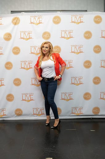 Woman in orange blazer and jeans by Windy City Live background