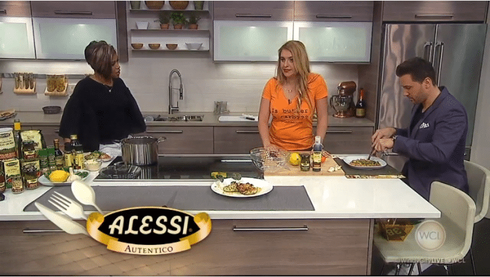 Mila in studio kitchen with tv hosts making food