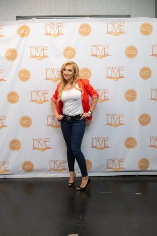 Mila in an orange blazer and jeans standing in front of Windy City Live backdrop